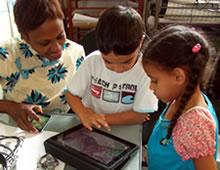 Three children gathered around, looking at a tablet.