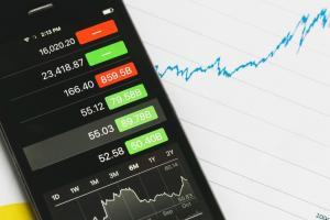 smartphone with stock prices and graph in blue ink