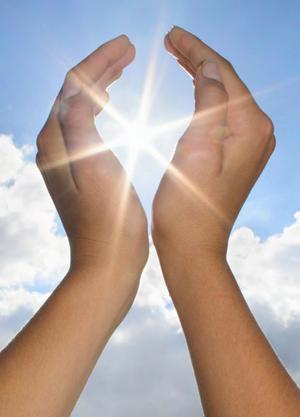 Image of sun shining through gap in hands