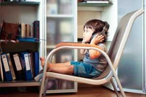 Toddler sits in chair and wears large stereo headphones