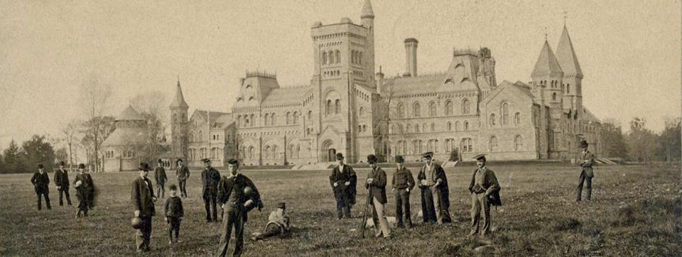 Old photo of people standing on grass in front of University College