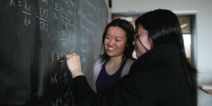 Photo of two students solving an organic chemistry problem on a blackboard