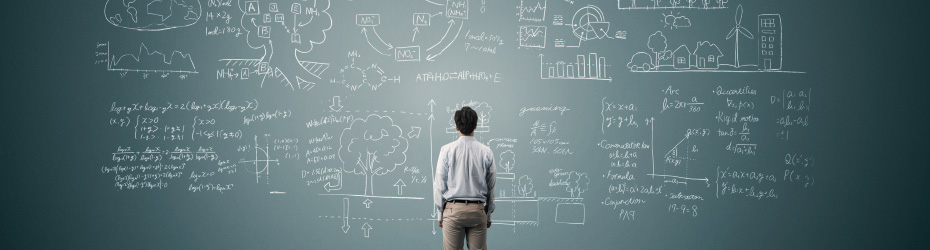 Image of a man standing in front of a blackboard full of facts and figures
