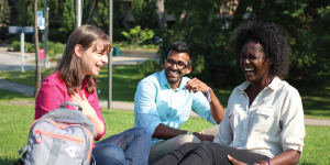 Photo of three students on campus green