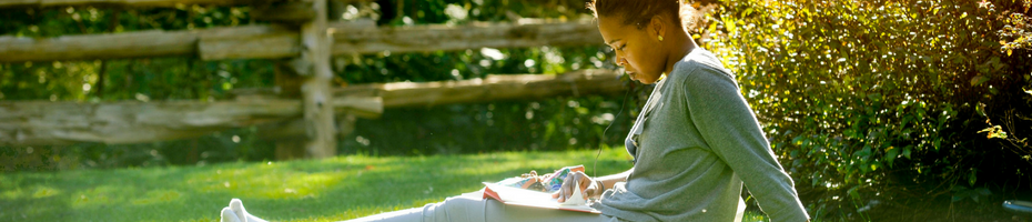 A student reading a book outside while sitting on grass.
