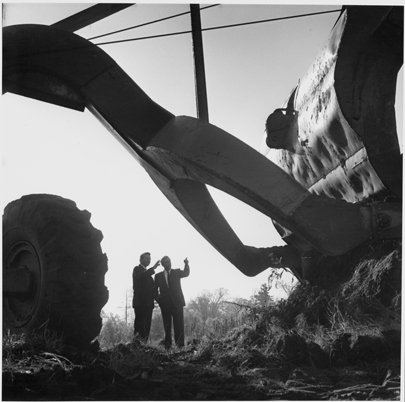 Bill Davis on left and Dr. Carleton Williams on right, stand under heavy machinery