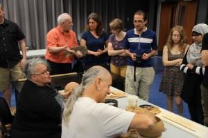 Wendat Pottery Workshop, participants standing in a circle watching demonstration of pottery making