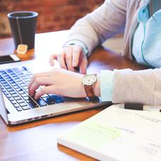 woman working on laptop with book nearby