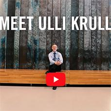 "Ulli Krull sitting on bench in Instructional Building, text overlay reads ""Meet Ulli Krull"", red and white arrow implies playable video"
