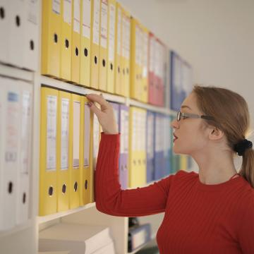 Image of woman looking through archival material